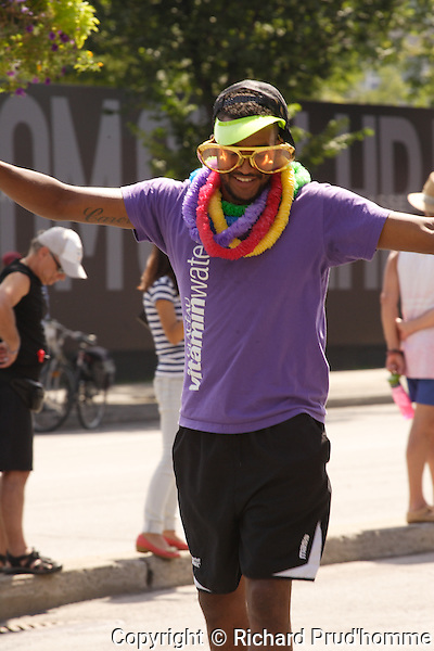 a young male adult is happy to particiapte in the Pride Parade