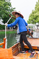 Suzhou, Jiangsu, China.  Middle-aged Woman Rowing Boat for Visitors on a Canal in Tongli Ancient Town near Suzhou.