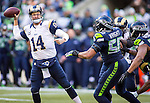 St. Louis Rams  quarterback Shaun Hill (14) scrambles while being pressured by Seattle Seahawks linebackers K.J. Wright (50) and Michael Bennett (72) at CenturyLink Field in Seattle, Washington on December 28, 2014.  The Seahawks officially wrapped up the No. 1 seed in the NFC playoffs shortly after beating the Rams, 20-6. Despite the Cowboys and Packers also winning to finish 12-4, the Seahawks (12-4) won the multi-team tiebreaker and earned home-field advantage throughout the playoffs for the second consecutive season.  ©2014. Jim Bryant Photo. All Rights Reserved.
