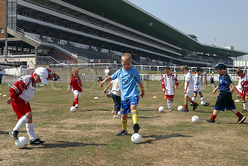 August 09, 2003: Children practising their ball skills during the soccer masterclass in the summer silver ring. The Blue Square Shergar Cup. Ascot Photo: Neil Tingle/Action Plus...Horse Racing 030809 flat teams kids child boys girls football grandstand