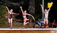 Three young girls jumping off a dock in cottage country Ontario