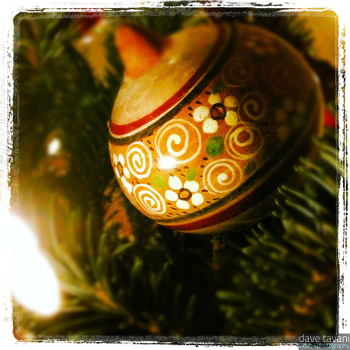 An antique looking Christmas ball is illuminated by a light on our tiny Christmas tree.
