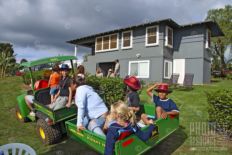 Kids have fun on a tractor ride at a company party in upcountry Kula.