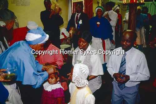 Mount Zion Spiritual Baptist church North London UK. Mother Noel  anoints members of the congregation This church service takes place in the front room of a small terraced house in north London. It is not entirely Christian.