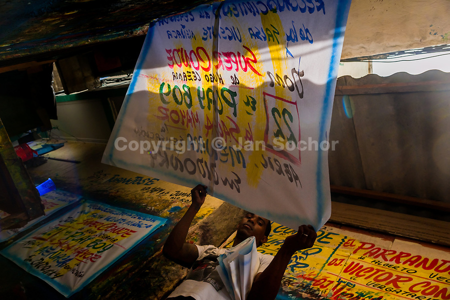 """A Colombian sign painter takes down a just-finished music party poster in the sign painting workshop in Cartagena, Colombia, 17 April 2018. Hidden in the dark, narrow alleys of Bazurto market, a group of dozen young men gathered around José Corredor (""""Runner""""), the master painter, produce every day hundreds of hand-painted posters. Although the vast majority of the production is designed for a cheap visual promotion of popular Champeta music parties, held every weekend around the city, Runner and his apprentices also create other graphic design artworks, based on brush lettering technique. Using simple brushes and bright paints, the artisanal workshop keeps the traditional sign painting art alive."""