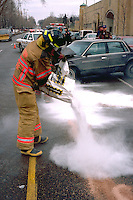 Fireman spreading anti-fire material at emergency car accident site.  St Paul Minnesota USA