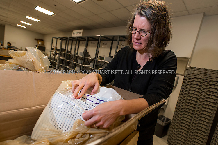 10/30/2012--Seattle, WA, USA..Stephanie Lamson, 44, a preservation librarian for the University of Washington Libraries, works at the University's Suzzallo Allen library receiving room with two boxes of newly-arrived books that were recently frozen to kill bed bugs. Here she opens the boxes to inspect the books to make sure the bed bugs are dead...©2012 Stuart Isett. All rights reserved.