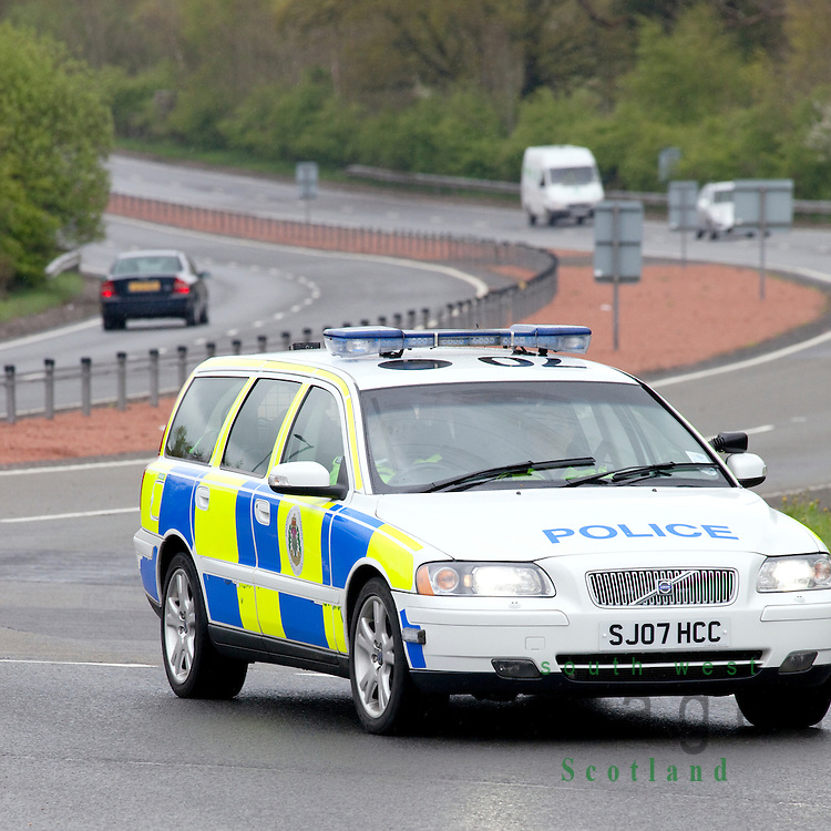 Road traffic police car Volvo on the A75 coming around a roundabout near Dumfries Scotland UK