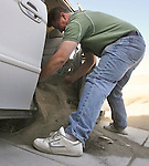 WIND23ripG.jpg.( 10/22/07, San Jacinto, Metro ) Dan Benedic, 41, of Rancho Cucamonga, helps Abbey Hernandez, remove the blow sand from her van at the 1000 block of Blodgett Street in San Jacinto on Monday, October 22, 2007. Many of the houses on this street have no electricity. (The Press-Enterprise/Rodrigo Pena)