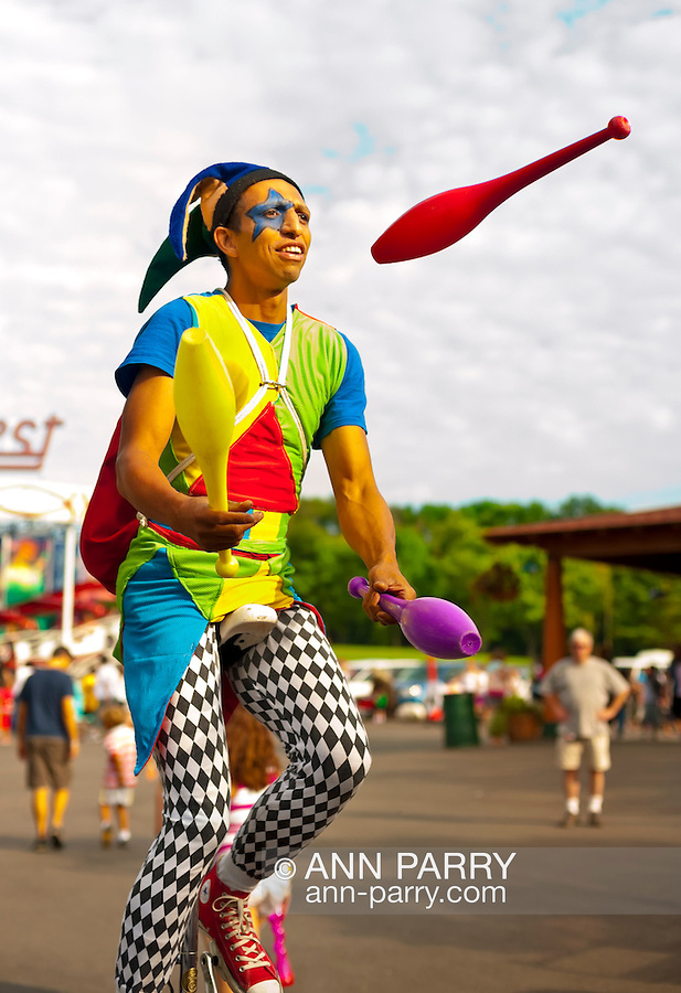 Aug. 25, 2012 - Middlebury, Connecticut, U.S. -- Juggler dressed in Harlequin costume juggles colorful pins as he rides unicycle throughout grounds of Quassy Amusement Park, to entertain those at park.
