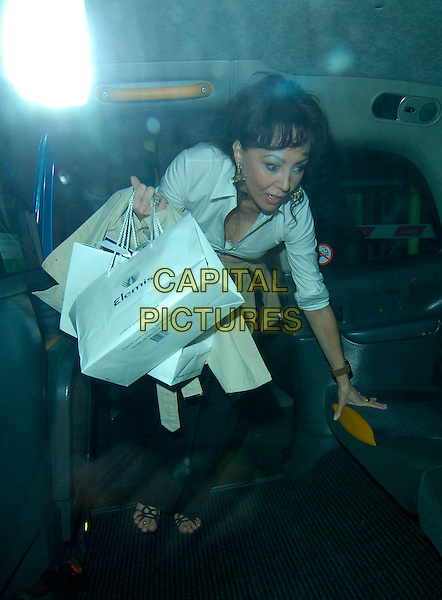 MARIE HELVIN.Marie Helvin's book launch party at The Ivy restaurant, London, England..October 29th, 2007.full length car cab taxi elemis goody funny face white shirt bags .CAP/CAN.©Can Nguyen/Capital Pictures