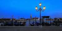 Gondalas on the grand canal with the background of San Giorgio Maggiore, and an early morning vaporetti ferry leaving the dock.