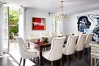 A spacious dining room styled in a traditional manner. Upholstered dining chairs are arranged around a polished wood table. Bold modern paintings bring a contemporary touch to the room.