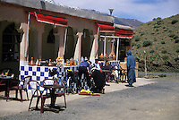 Atlas Mountains, Morocco - Roadside Rest Stop in the Atlas Mountains, between Marrakesh and Ouarzazate.  Snow is still on the mountains in April.  Cyclists checking their bikes.