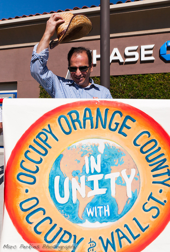 """Fred holds the primary """"Occupy Orange County, in unity with Occupy Wall Street"""" sign in front of a Chase Bank branch during the the Occupy Orange County, Irvine march to three banks on November 5.  He's even raising his hat to the camera."""