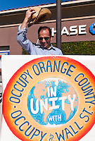 "Fred holds the primary ""Occupy Orange County, in unity with Occupy Wall Street"" sign in front of a Chase Bank branch during the the Occupy Orange County, Irvine march to three banks on November 5.  He's even raising his hat to the camera."