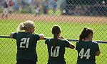 Female High school softball players watch a game from the outfield fence