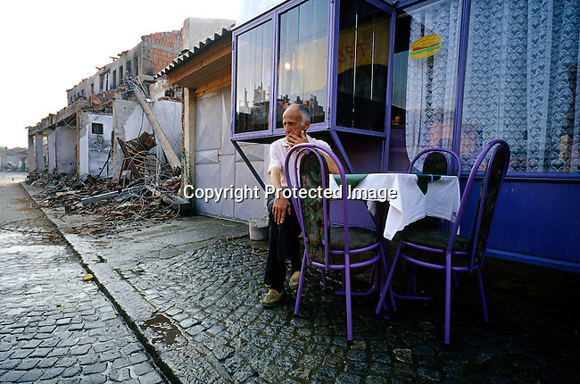 A man sits outside his café among the destroyed main street on June 25, 1999 in the old town in Djakovica, Kosovo. The area, mostly Muslim was heavily damaged by fires that the Serbs lit in retaliation of the NATO bombings of Serb positions during the Kosovo conflict in the spring of 1999. (Photo by: Per-Anders Pettersson)