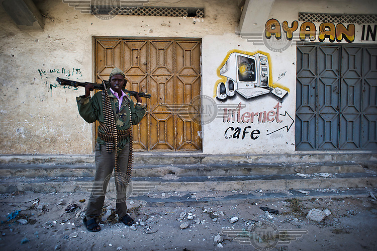 A militiaman stands with a gun near a sign for an internet cafe on a street in Mogadishu. Although Al Shabab have been driven out of the city, security is still an issue.