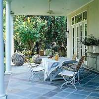 The porch is furnished with tasteful garden chairs and a trestle table and the floor is laid with slate tiles