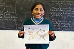 School girl holding up paper with colored animals during an educational outreach program, Ciudad de Piedra, Andes, western Bolivia
