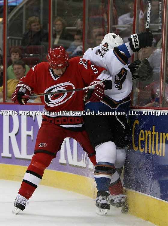 Carolina's Frantisek Kaberle (5) checks Washington's Rico Fata (20) into the boards on Wednesday, March 29, 2006 at the RBC Center in Raleigh, North Carolina during a regular season NHL game. The Washington Capitals defeated the Carolina Hurricanes 5-1.