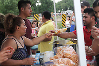 MEGAN DAVIS MCDONALD COUNTY PRESS/Alejandra Morales serves elote to a hungry customer during last year's Third of July Celebration. Morales and her family were preparing a variety of flavorful, cultural dishes for attendees.