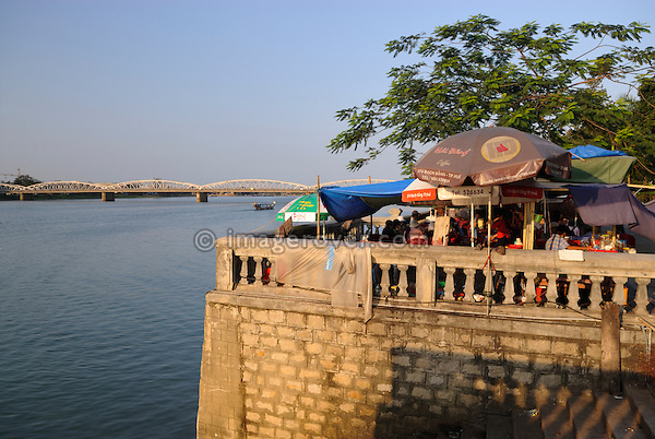 Asia, Vietnam, Hue. Busy food stall at the river Huong (Perfume River) overseeing the Trang Tien bridge.