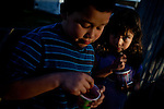 Nine-year-old Javier Hernandez, left, and his sister, Elizabeth, 6, eat ice cream in the Parklawn neighborhood in Modesto, Calif., February 22, 2012.
