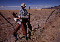 "Lending his weight, Zed Davies helps his father, Stacy, mend fences on Roaring Springs Ranch, not far from Steens Mountain in Oregon. Ranchers and environmentalists mended fences of their own to reach a mixed-use plan for the area. ""Everybody got a little bit of what they wanted,"" says Davies. In complex land exchanges, ranchers gained public acreage as private land ?  more than 60,000 acres in the case of Roaring Springs Ranch."