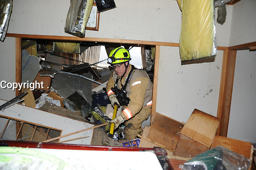 A member of the Fairfax County Urban Search and Rescue Team pushes aside furniture and ruble while looking for survivors, here, following an 8.9-magnitude earthquake, which triggered a devastating tsunami through this Japanese coastal city. Teams from the United States, United Kingdom and China are on scene to assist in searching for missing residents.