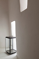A contemporary portable lantern has been placed in one of the niches in this smooth whitewashed wall