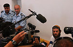 Neria Ofan, a settler in the unauthorized Israeli outpost of Givat Lehava, West Bank, is circled by press before a hearing in his case at an Israeli court in Be'er Sheva. Neria Ofan got a 6-months administrative detention, prior to the implementation of the Israeli pullout from Gaza.