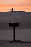 Flames are seen on a grill in a parking area as people watch the sunset at White Sands National Monument near Alamogordo, New Mexico, USA, on Sat., Dec. 30, 2017.