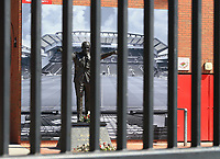 May 4th 2020, Liverpool, United Kingdom; Anfield stadium during the suspension of the Premier League due to the Covid-19 virus pandemic; the statue of former manager Bill Shankly behind the padlocked gates of the Kop entrance