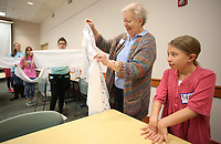 NWA Democrat-Gazette/DAVID GOTTSCHALK  Vivian Bertram (right), 10, watches as Jane Millette demonstrates Tuesday, March 20, 2018, how to line up the right edges during the first session of the Sewing Club Workshop at the Springdale Public Library. Participants, ages 10-14, in the two day workshop are making are learning the use of a sewing machine and fabric techniques as they make a pillowcase and an overnight bag.