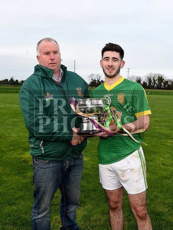 Curraha captain Danny Battersby is presented with the under 21 Football Championship trophy by Vice Chairperson of Meath County Board Peter O'Halloran after beating Wolfe Tones in the final. Photo: Colin Bell/pressphotos.ie