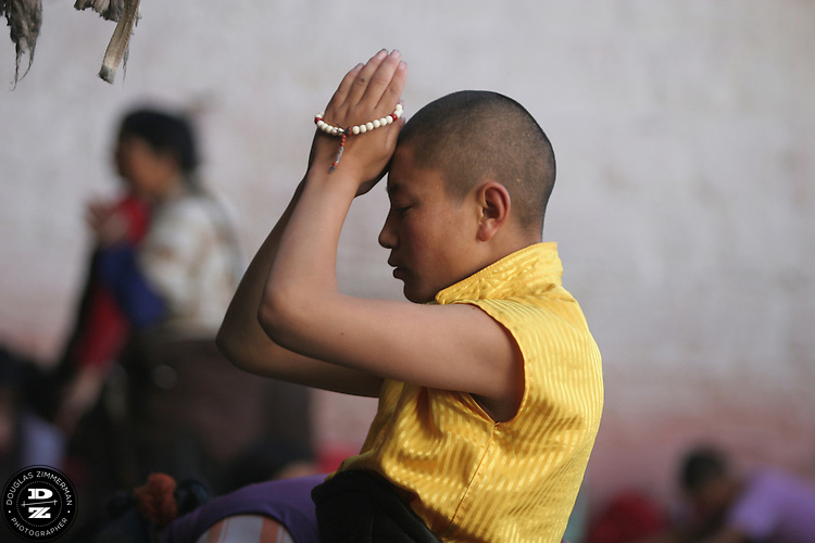 A Buddhist pilgrim prays in front of the Jokhang (also known in Tibetan as Tsuglhakhang) at  Barkhor Square in Lhasa, Tibet. The Jokhang is considered the most revered religious structure in Tibet.  Photograph by Douglas ZImmerman