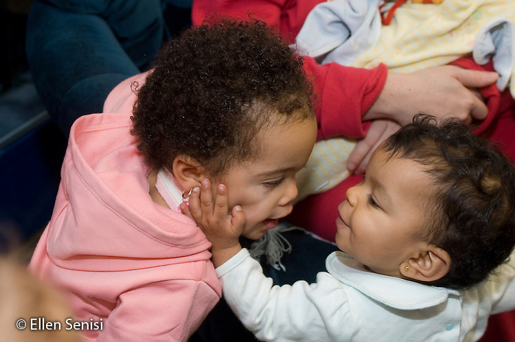 MR / Schenectady, NY.Schenectady Day Nursery / private non-profit daycare center / Infant Class.Toddler (girl, 1, African-American / Caucasian) and infant (girl, 8 months) interact and touch each other..MR: Par4, Far3.© Ellen B. Senisi
