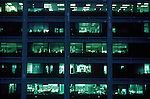 Building exterior of office windows lit at night. New York NY.