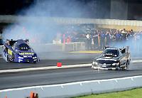 Jun. 2, 2012; Englishtown, NJ, USA: NHRA funny car driver Mike Smith (left) goes sideways alongside Cruz Pedregon during qualifying for the Supernationals at Raceway Park. Mandatory Credit: Mark J. Rebilas-