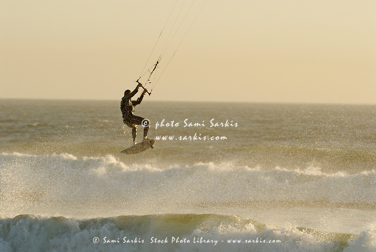 Man kitesurfing on high waves at sunset, Cape Town, South Africa