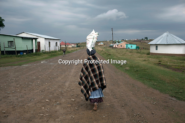 MVEZO, SOUTH AFRICA - MARCH 28: A woman walks with food in a bag on her head in the village on March 28, 2012 in Mvezo South Africa. Nelson Mandela was born in this rural village in 1918 and moved to nearby Qunu as a young boy. Qunu is about 32 kilometers away. The village is now headed by his grandson Mandla Mandela. (Photo by Per-Anders Pettersson)