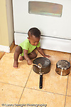 12 month old baby boy in kitchen hitting pot with metal spoon, playing with pots and pans