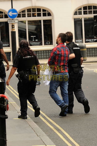 **Exclusive**<br /> Officers leading away a possible illegal worker <br /> From The Breakfast Club cafe in Soho Where Immigration Enforcement offers took an alien, London, UK, 8th August 2013.<br /> **Exclusive All-Rounder**<br /> full length arrested arrest UK Boarder Agency politics police policing government <br /> CAP/IA<br /> &copy;Ian Allis/Capital Pictures