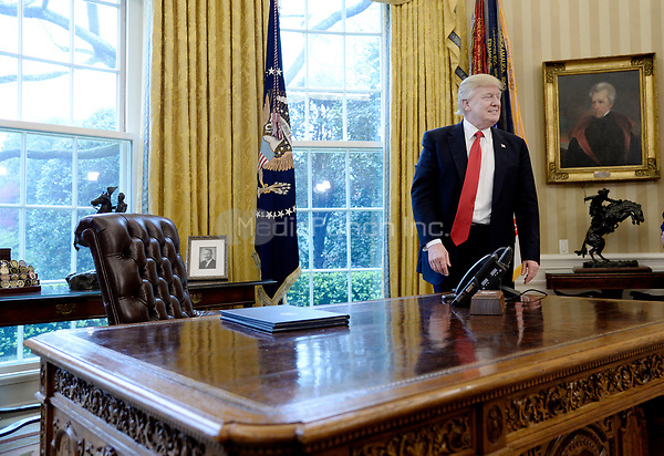 United States President Donald Trump stands in the Oval Office after speaking about trade at the White House March 31, 2017 in Washington, DC. <br /> Credit: Olivier Douliery / Pool via CNP /MediaPunch