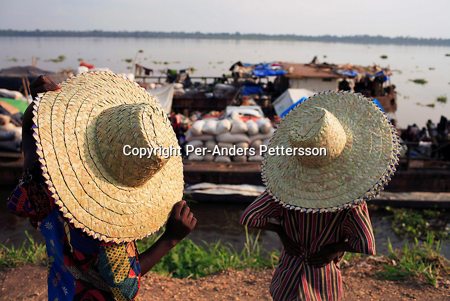 BUMBA, DEMOCRATIC REPUBLIC OF CONGO MARCH 25: Two girls sell straw hats in the port on March 25, 2006 in Bumba, Congo, DRC. The girls are trying to sell hats to passengers traveling on a boat from Kisangani to Kinshasa, a journey of 3-7 weeks. Congo River is a lifeline for millions of people, who depend on it for transport and trade. During the Mobuto era, big boats run by the state company ONATRA dominated the traffic on the river. These boats had cabins and restaurants etc. All the boats are now private and are mainly barges that transport goods. The crews sell tickets to passengers who travel in very bad conditions, mixing passengers with animals, goods and only about two toilets for five hundred passengers. The conditions on the boats often resemble conditions in a refugee camp. Congo is planning to hold general elections by July 2006, the first democratic elections in forty years..(Photo by Per-Anders Pettersson)..