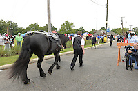 """5/30/15 Indianola,. Fans lined the street to see B.B. Kings final homecoming funeral procession outside the BB King Museum. A family member reaches out to touch the casket for one last time at the gravesite of Mr. King during the burial outside in the rain. The Thrill is gone, the casket holding the body of BB King arrives at the Bell Grove Missionary Baptist Church for his final homecoming. Blues legend B.B. King is is laid to rest in the shadow of the cotton gin at the B.B. King Museum and Interpretive Center. Mr King's final homecoming procession included a black horse WITH A saddle flanked with two of BB's famous """"Lucielle"""" guitars signed by Mr. King. Fans lined the streets to watch the procession and pay their respect to the King of the Blues. Photo ©Suzi Altman"""