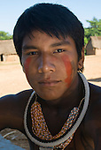 Pará State, Brazil. Aldeia Pukararankre (Kayapo). Young warrior with red urucum face paint and bead and tooth necklaces.