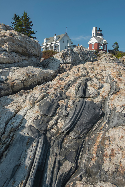 "Below Pemaquid Point Lighthouse lies this ""frozen wave"" rock formation of metamorphic and igneous rocks with veins of quartz mixed with slabs of schist and gneiss running all the way down into the sea."